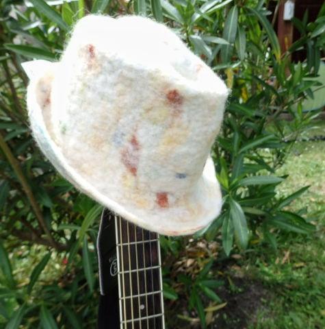 trilby blanc tacheté couleur posé sur le manche de la guitare