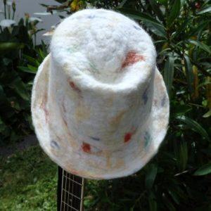 trilby blanc posé sur manche de guitare