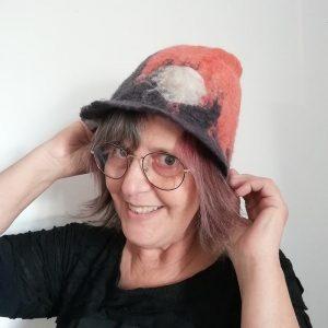chapeau cloche orange et noir avec un rond blanc représentant la lune